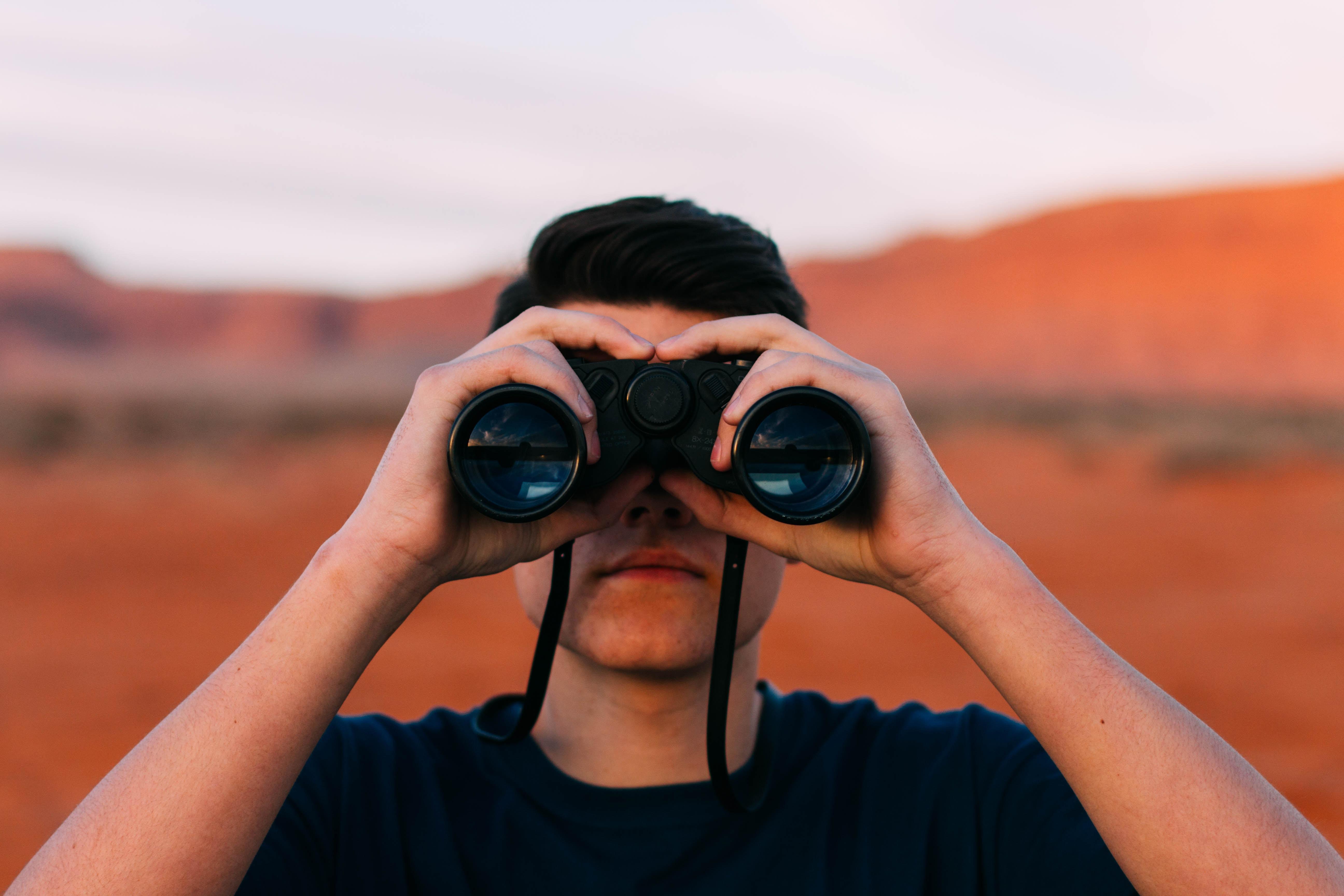 man facing the camera looking through binoculars