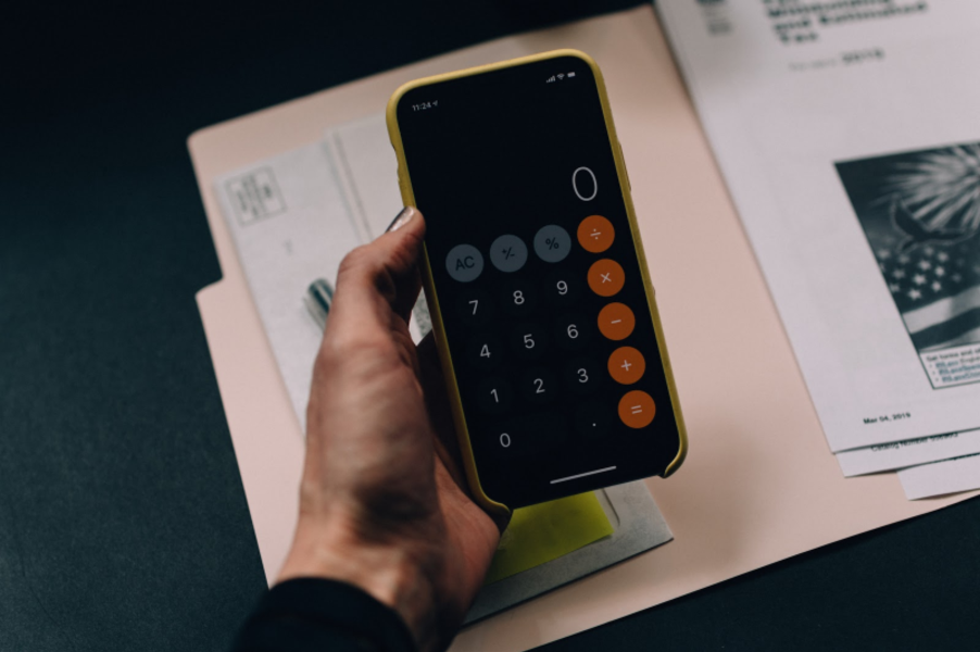 person holding a calculator working out their marketing budget